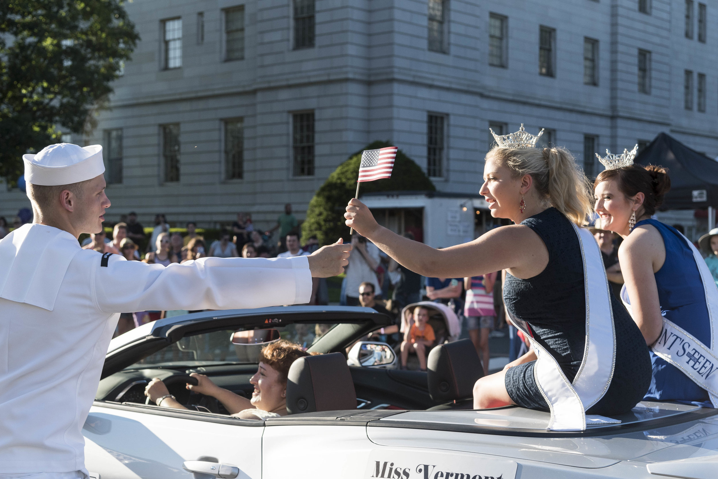 U.S.S. Montpelier sailor JD Smith (left) hands a miniature American flag to Miss Vermont, Julia Crane, during the Independence Day Parade in Montpelier on July 3rd, 2018.