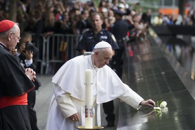 AP/John Minchillo- Pope Francis places a white rose at the South Pool of the 9/11 Memorial in downtown Manhattan, Friday, Sept. 25, 2015, in New York.