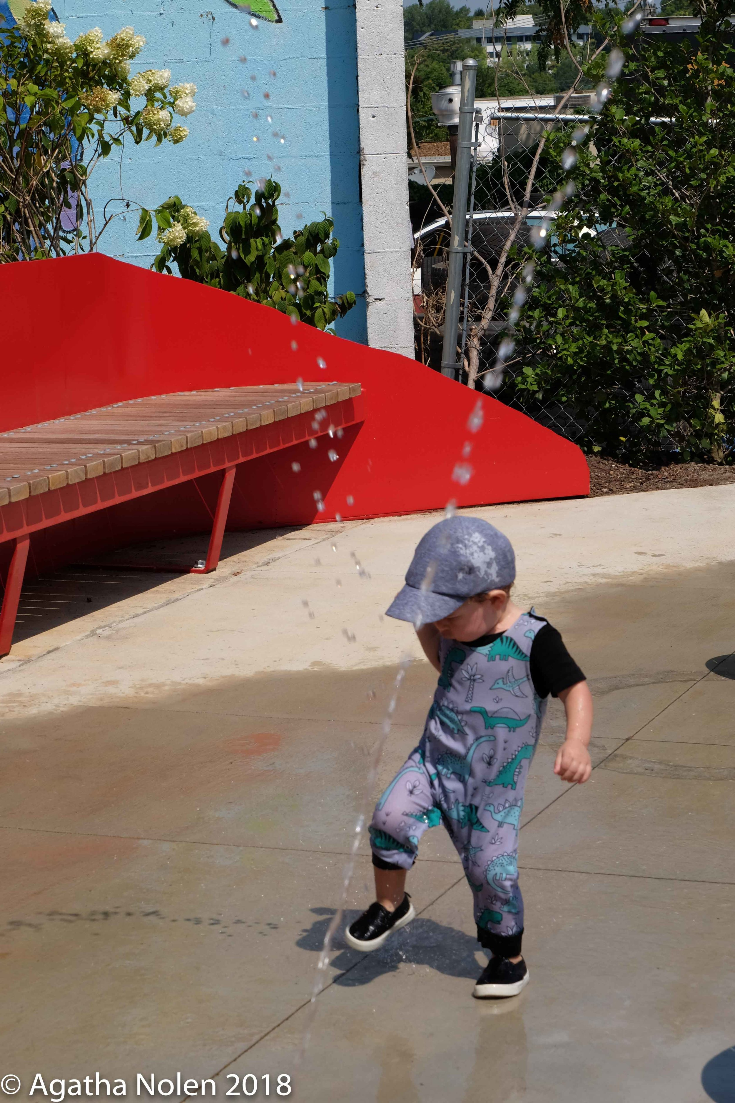 Boy playing in the waterfall at the dedication of Azafrán Park, Nashville, TN