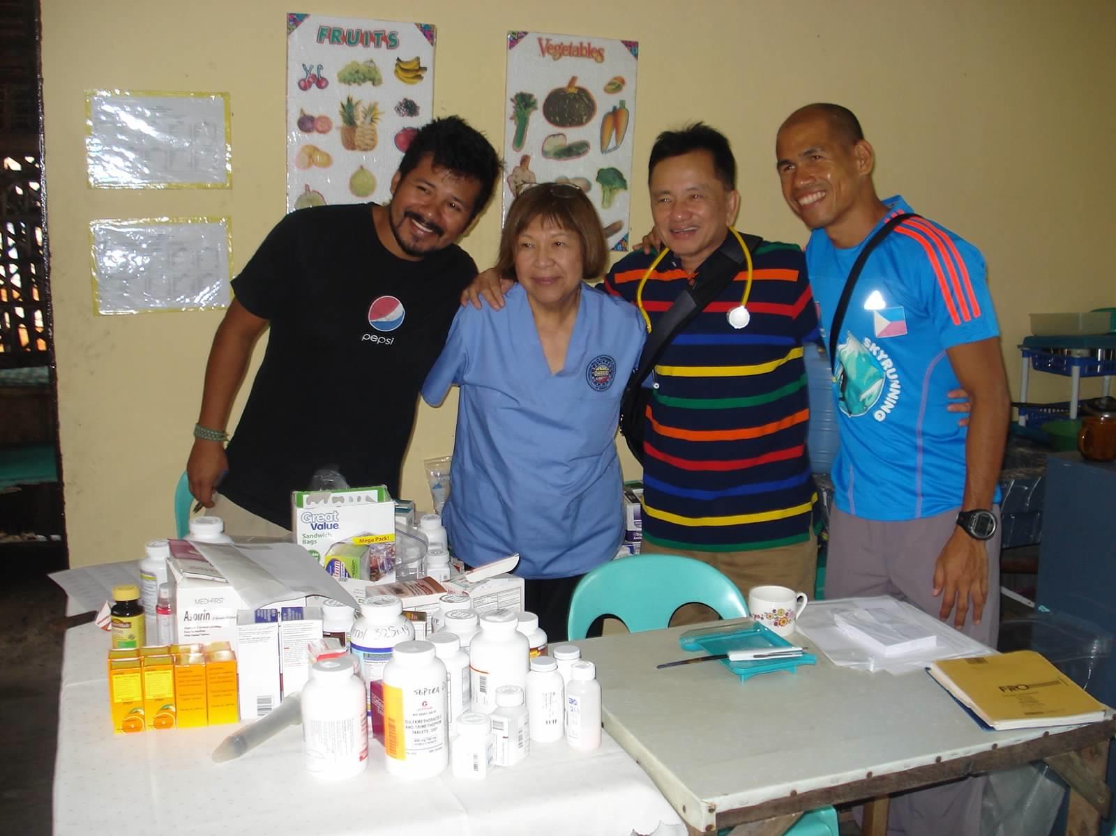 "Our pharmacy team: Eric Steiner, Peace Corps; Kay Yamagata, pharmacist; Ed Pangilinan, team administrator; ""Jun"" Ramirez, University of the Philiippines outreach team"