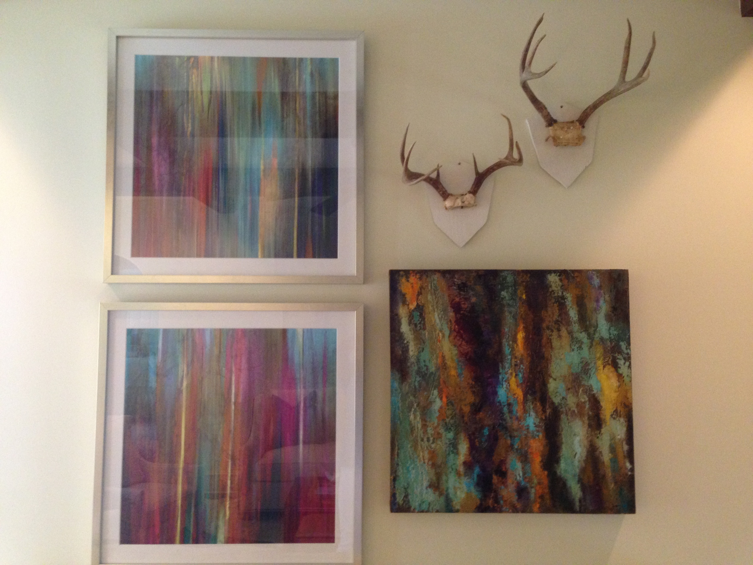 Two framed abstract prints paired with an original by Charlotte Caroom accented with two deer horns on white plaques