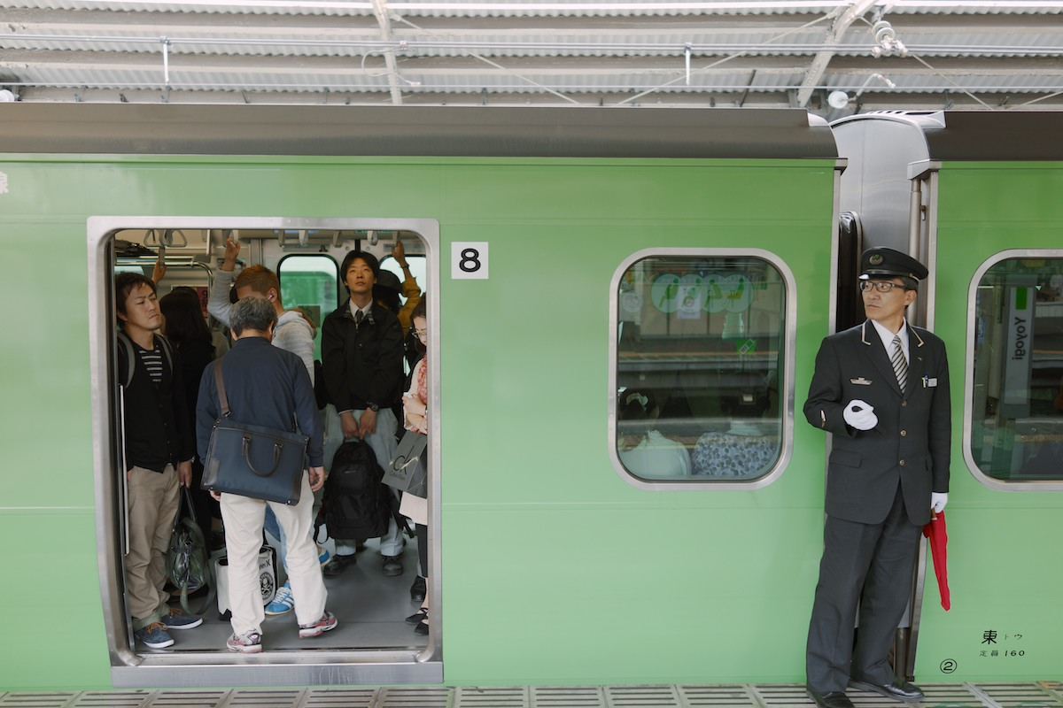 An attendant readies a train to leave Yoyogi station.