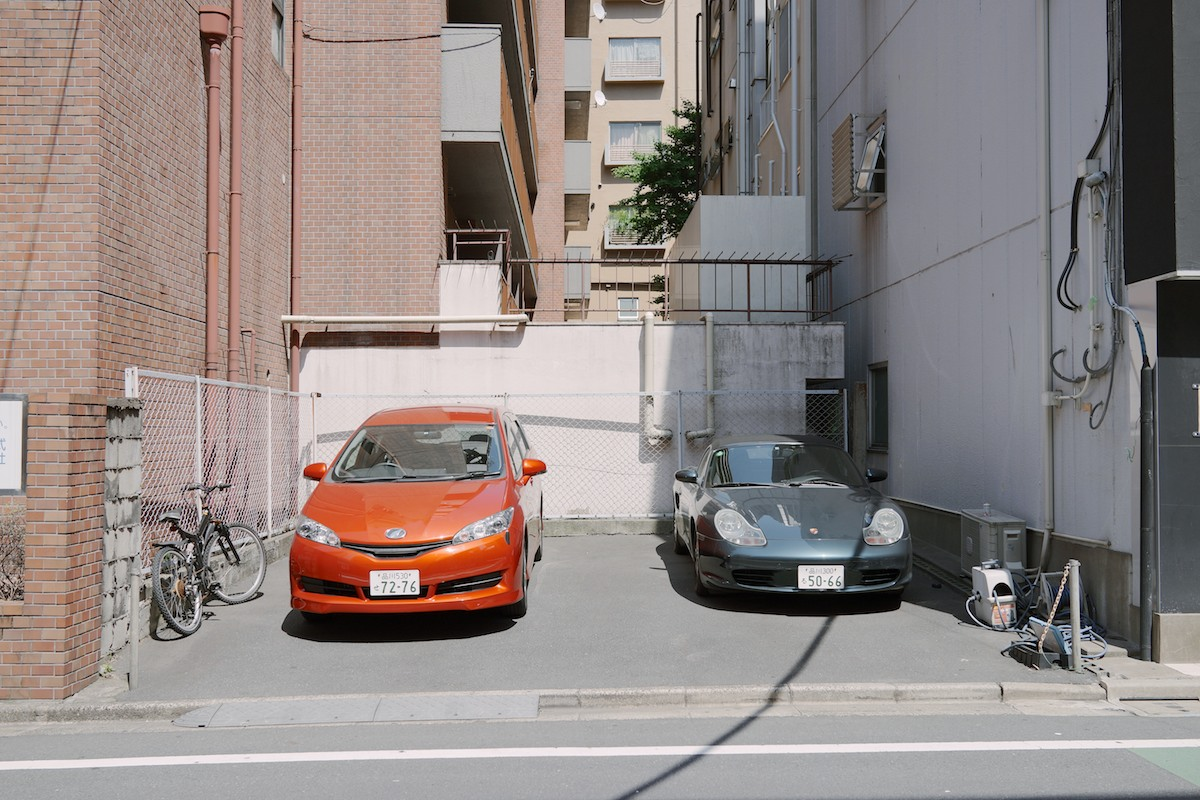 The Toyota Wish parked next to a Porsche Boxster.