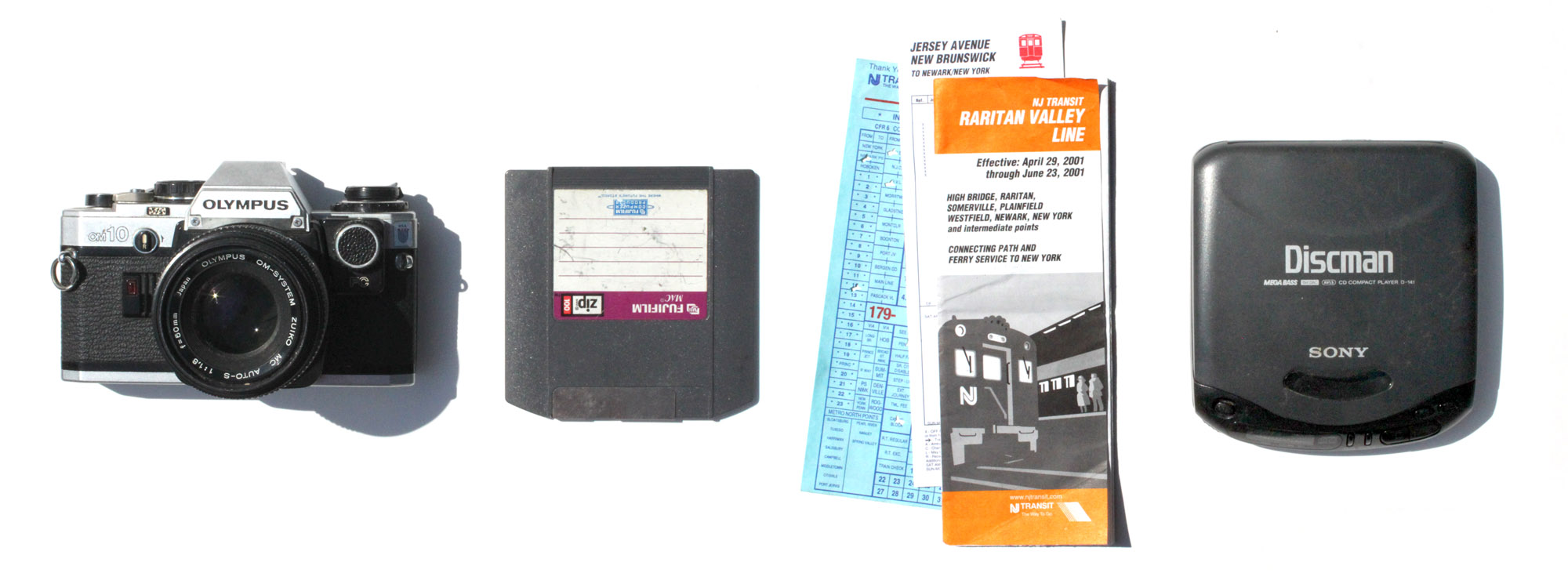 Mid 1970's Olympus SLR, Film Camera - 2001 ZIP Disk, Printed Train Schedule and a '90's era Discman.