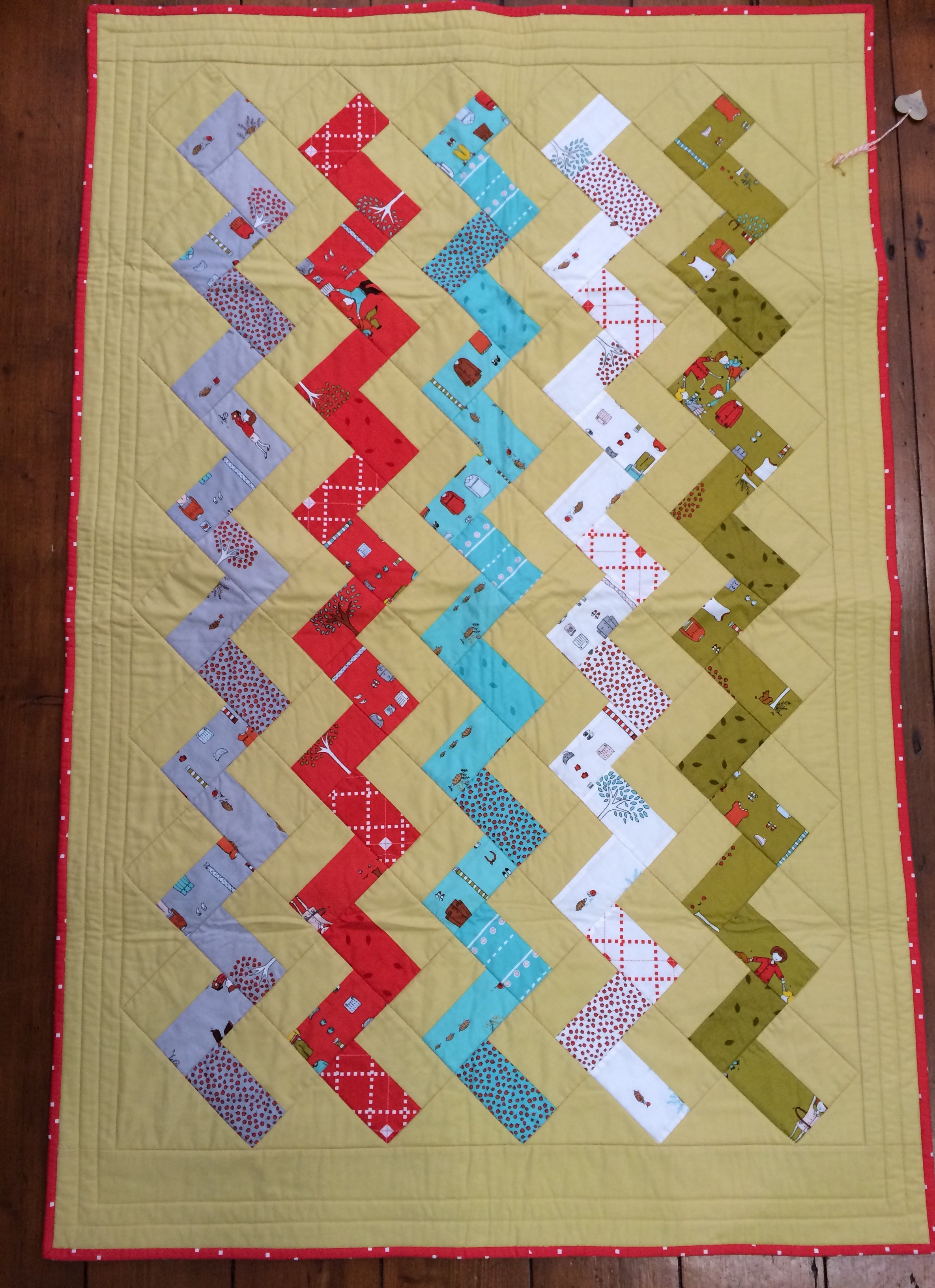 'Little Apples', by Aneela Hoey fabric in a Hettie's Patch pattern, 'A Chevron Baby Quilt'.