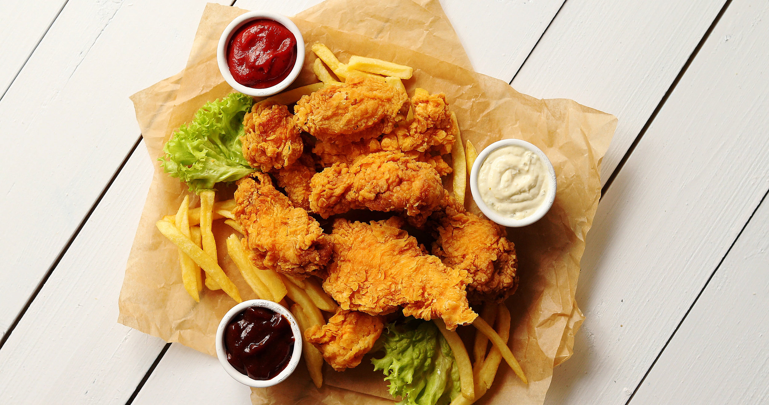 sauces-and-lettuce-near-french-fries-and-chicken-W4E6BNS.jpg