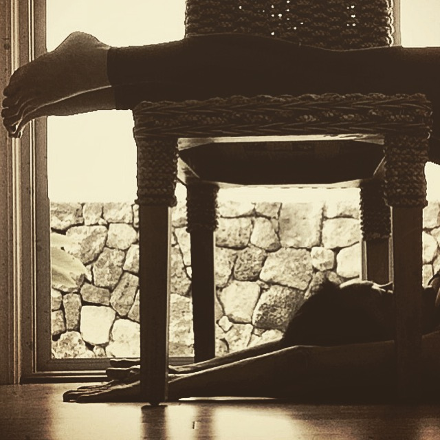 Supported Halasana, a restorative yoga pose.