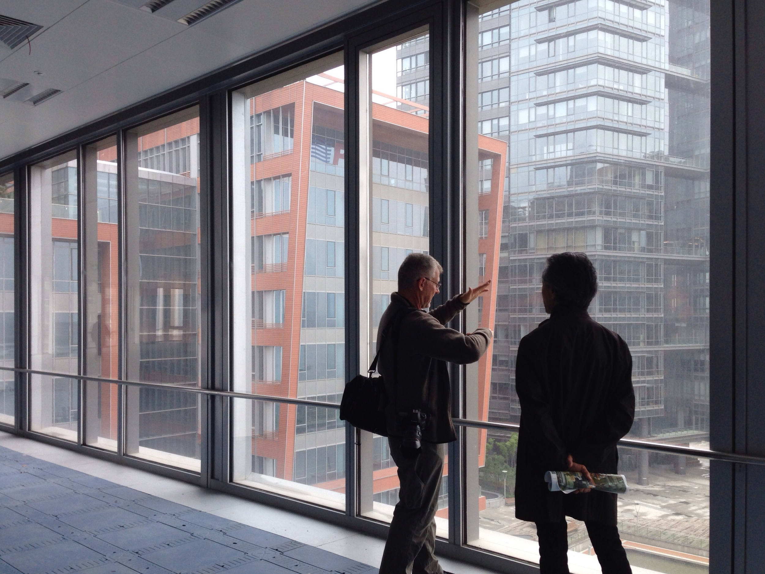 The photographer and architect discussing the project. You can see two of our buildings through the window, we are standing in a third and two more are out of view.