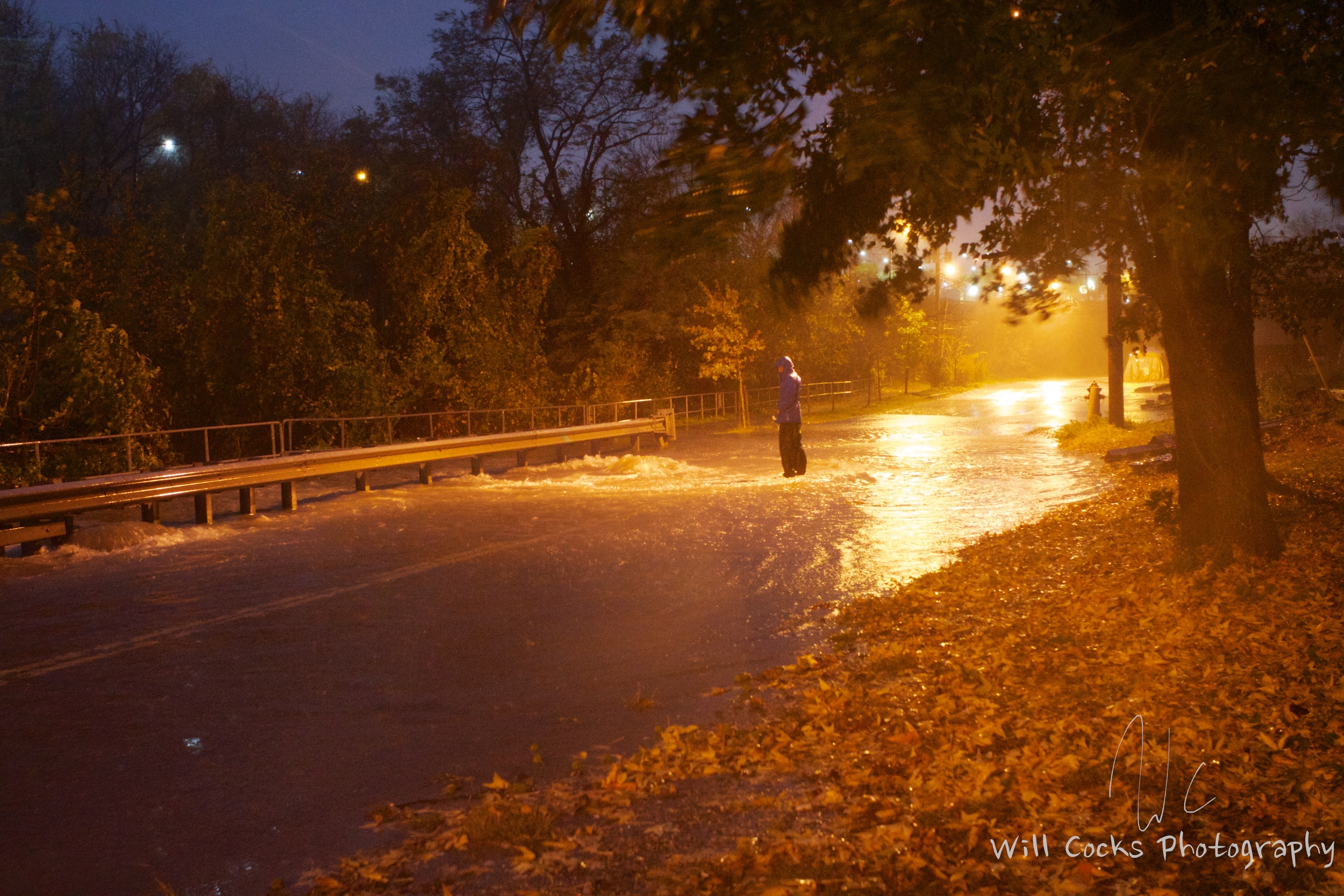A man stands on a flooded stretch of Falls Rd