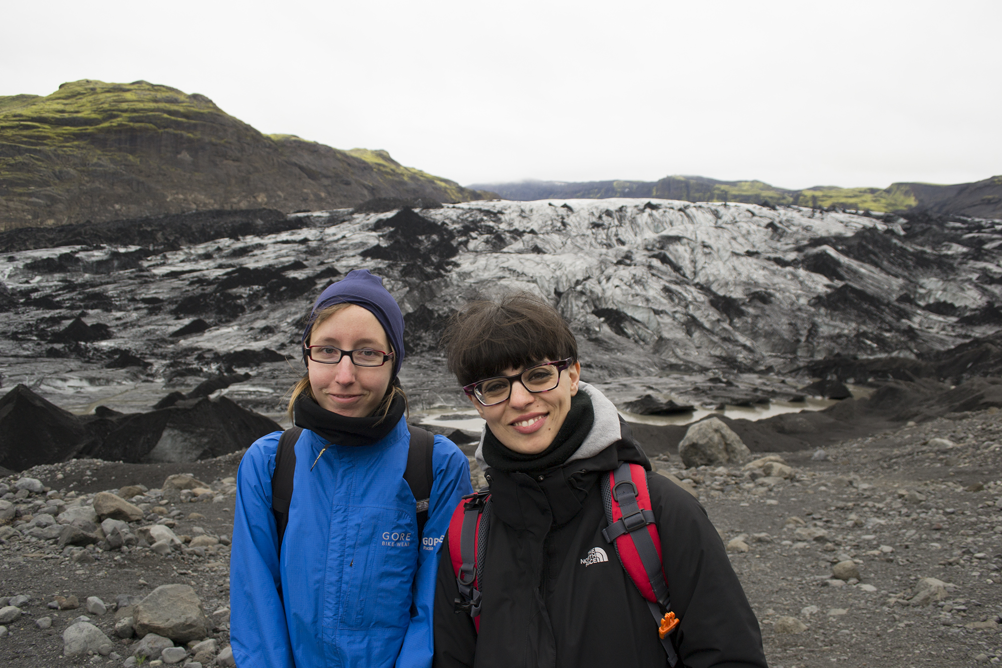 Maike Plenzke and Gloria Pizzilli stand in front of an incredible ash-covered glacier. - Photo by Jenny Wells