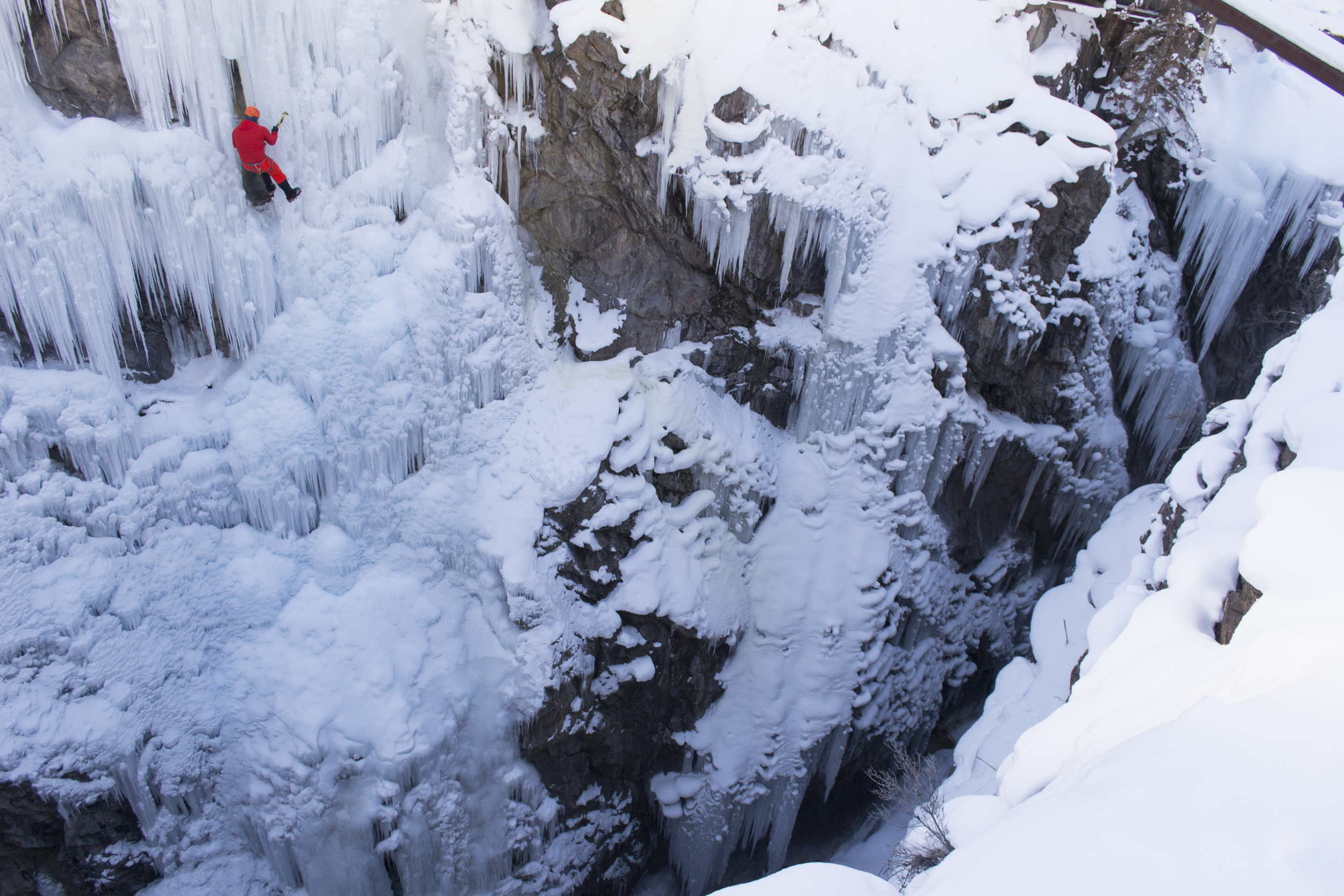 An experienced ice climber hovers over the icy gorge at the Ouray Ice Park.