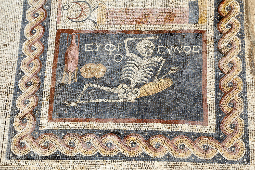"An ancient mosaic was discovered in Turkey of a skeleton with a glass of wine in one hand and resting on an elbow on a loaf of bread.  The writing says "" Be cheerful and live your life."""