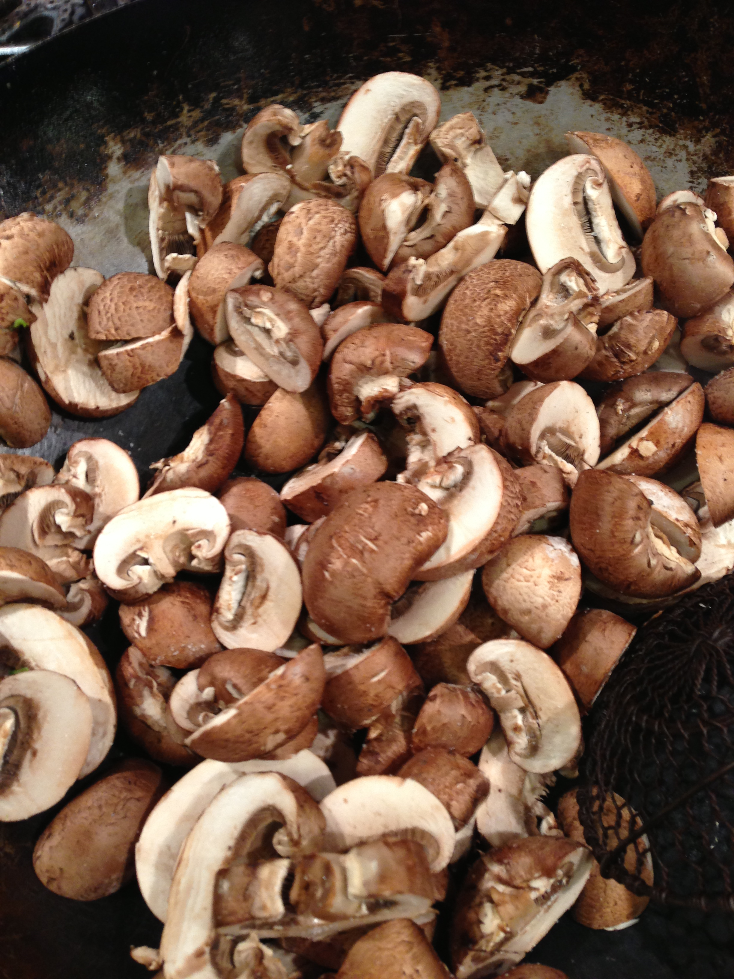 Now slice the mushrooms and sauté them until just done. In case no one has ever told you this, don't wash your mushrooms in water to clean them. I used to dump mine into a bowl of water to get the dirt off and I wondered why they were always so soggy. Mushrooms are like sponges and they soak up the water. Just use a cloth or paper towel to wipe off any soil. I cook my mushrooms in my dry wok on high heat. Because of the high moisture content of the mushrooms you don't need any oil or butter. Just add a little salt and stir until they're ready. After they're done, you can add any oil or butter or seasonings you like.