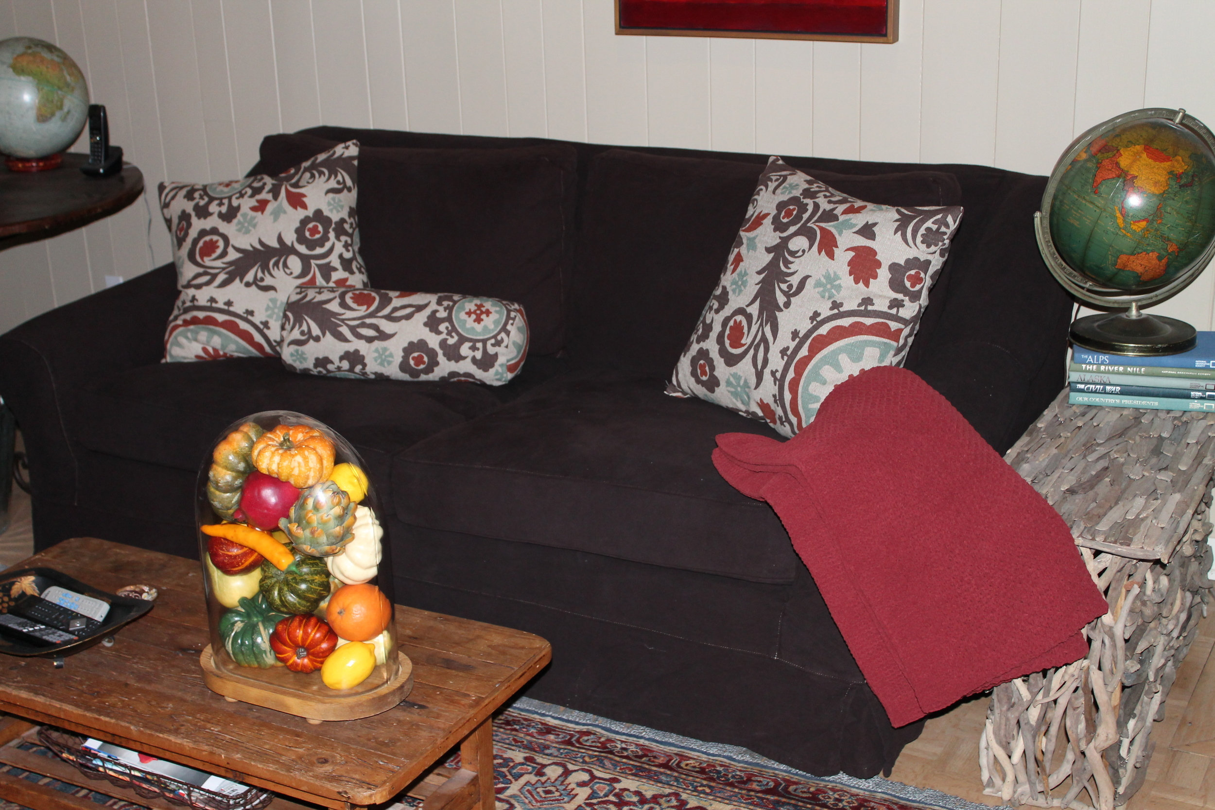 The natural linen slipcovers are removed and are replaced with dark brown, and darker pillows are added.