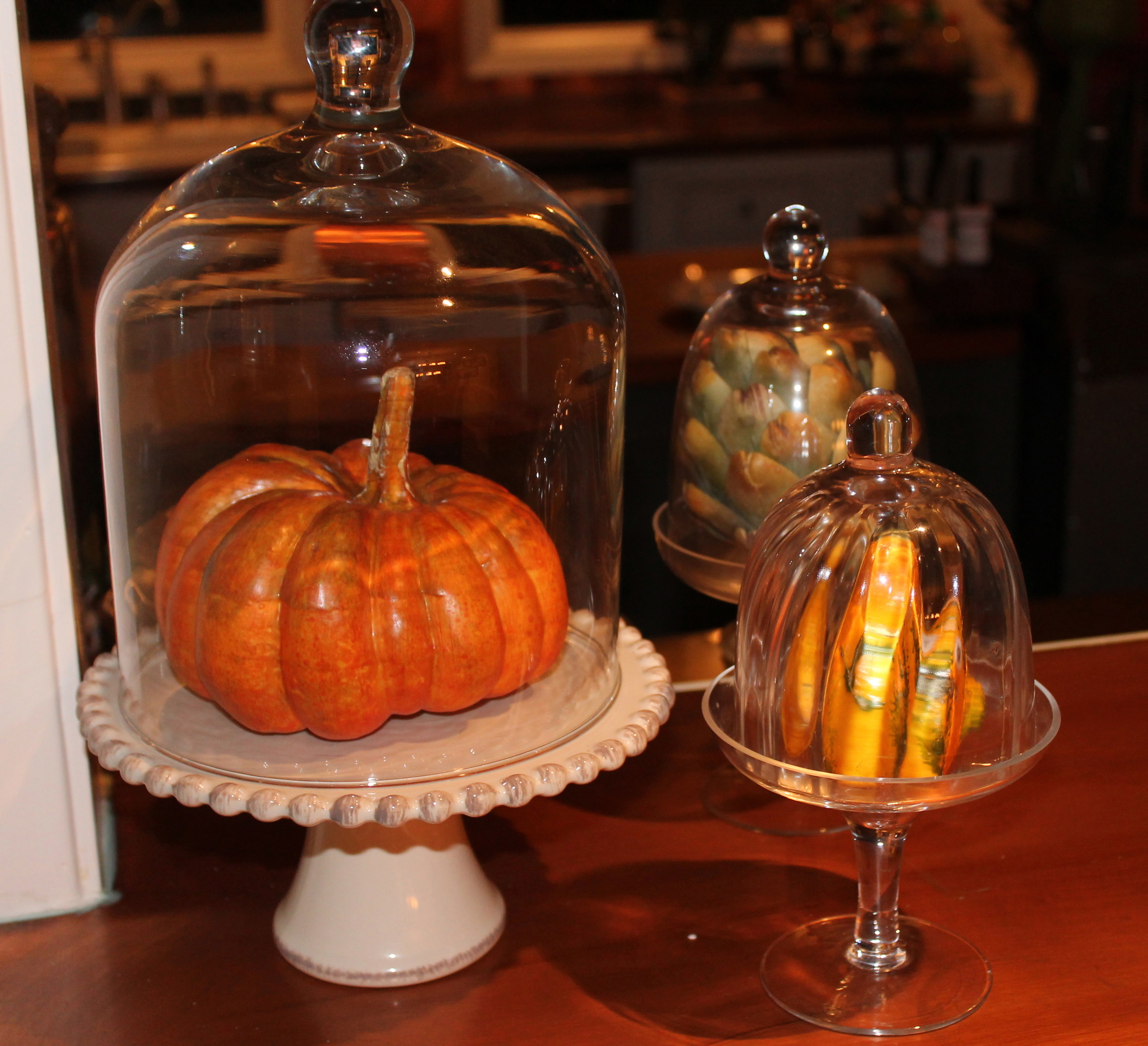 Even the kitchen counters get a touch of fall with gourds in cake domes.