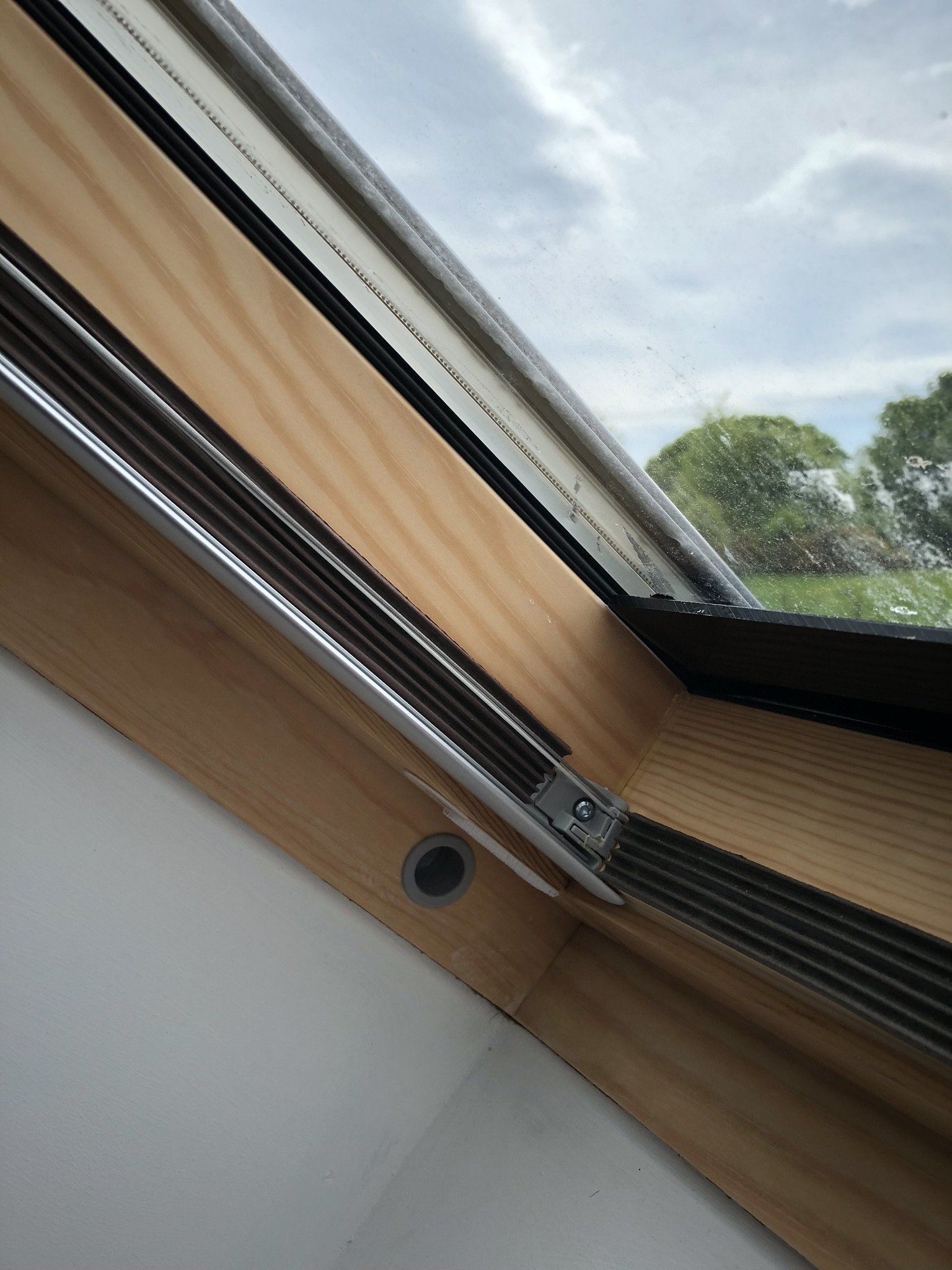 stick the E shape draught excluder down the side channel of the blind, flush with the front lip.