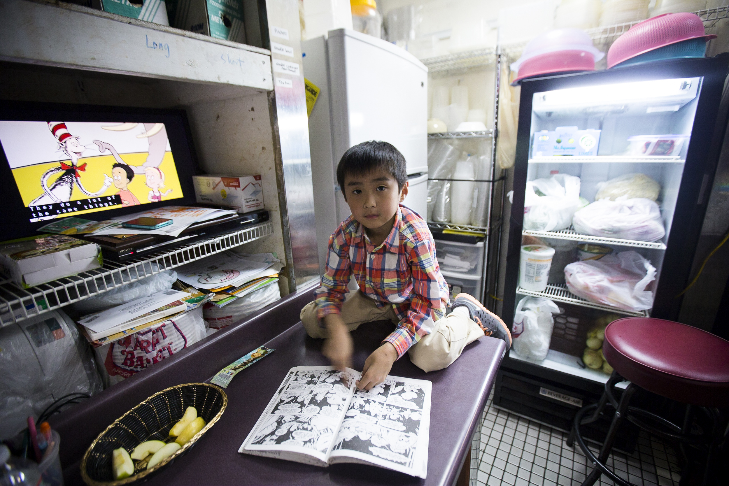 Henry Kyaw, 7. The son of Sai Kyaw reading comic books in a corner of the kitchen at Yoma. By Ann Wang