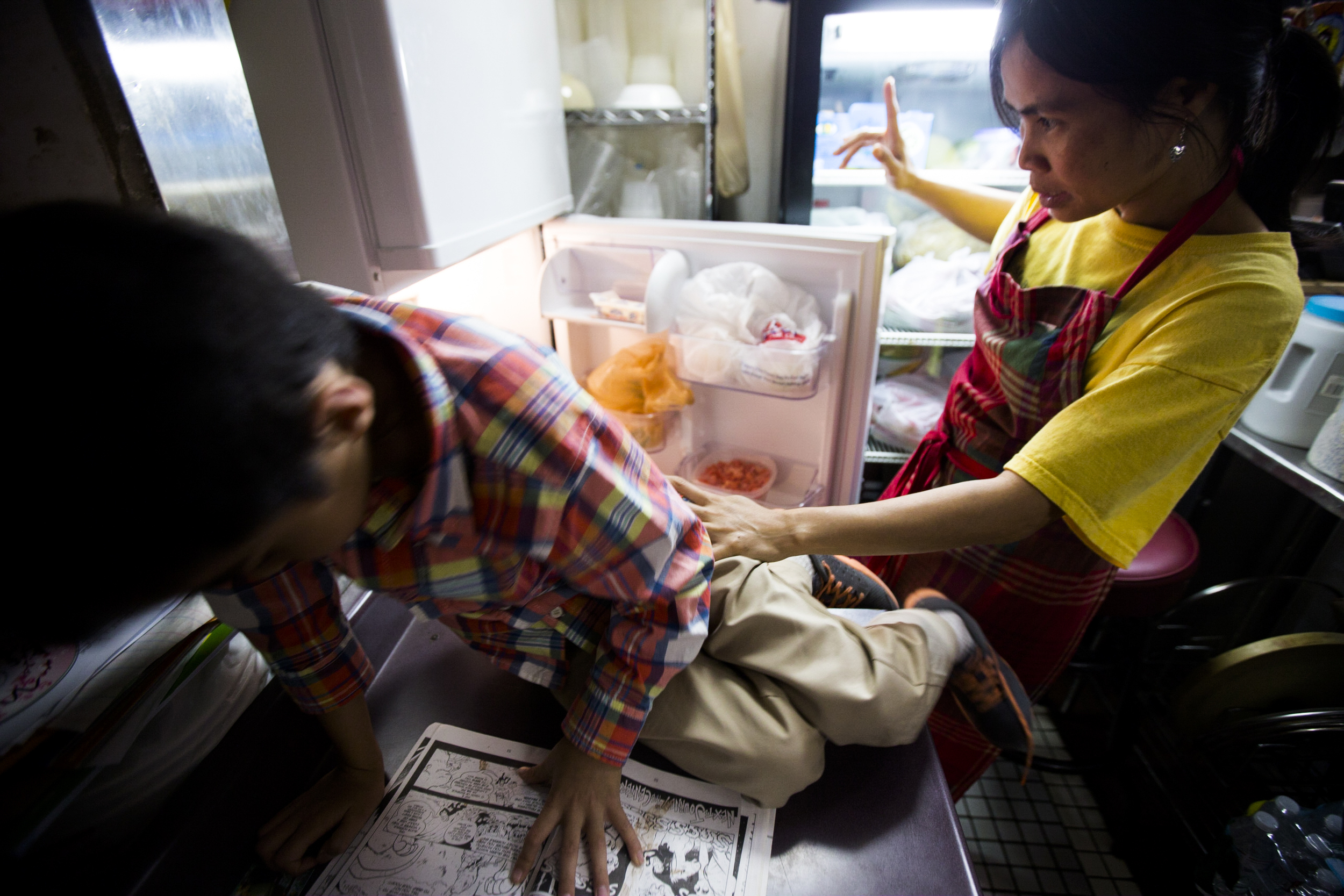 Thawdar Kway (R) collecting food from the fridge while talking to her son, Henry Kway (L). By Ann Wang