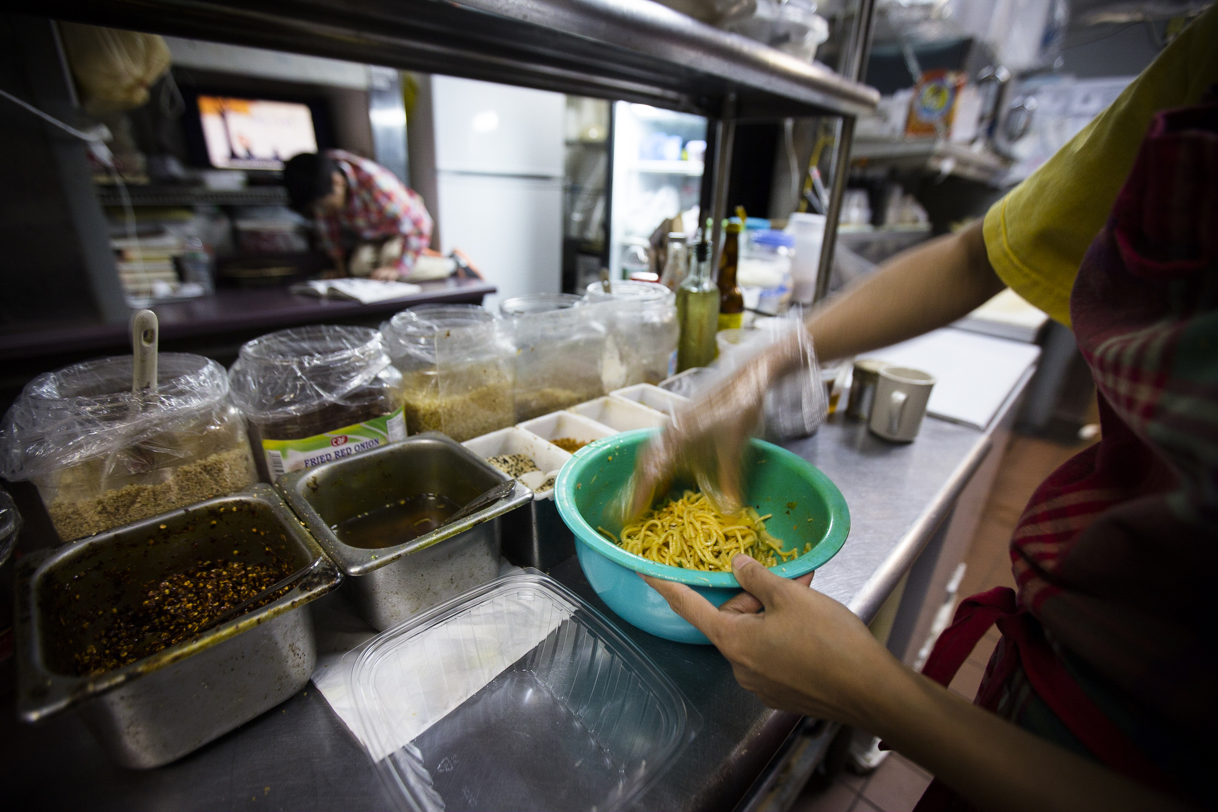 Thawdar Kway is mixing the noodles with spices to make Happy Noodle. By Ann Wang