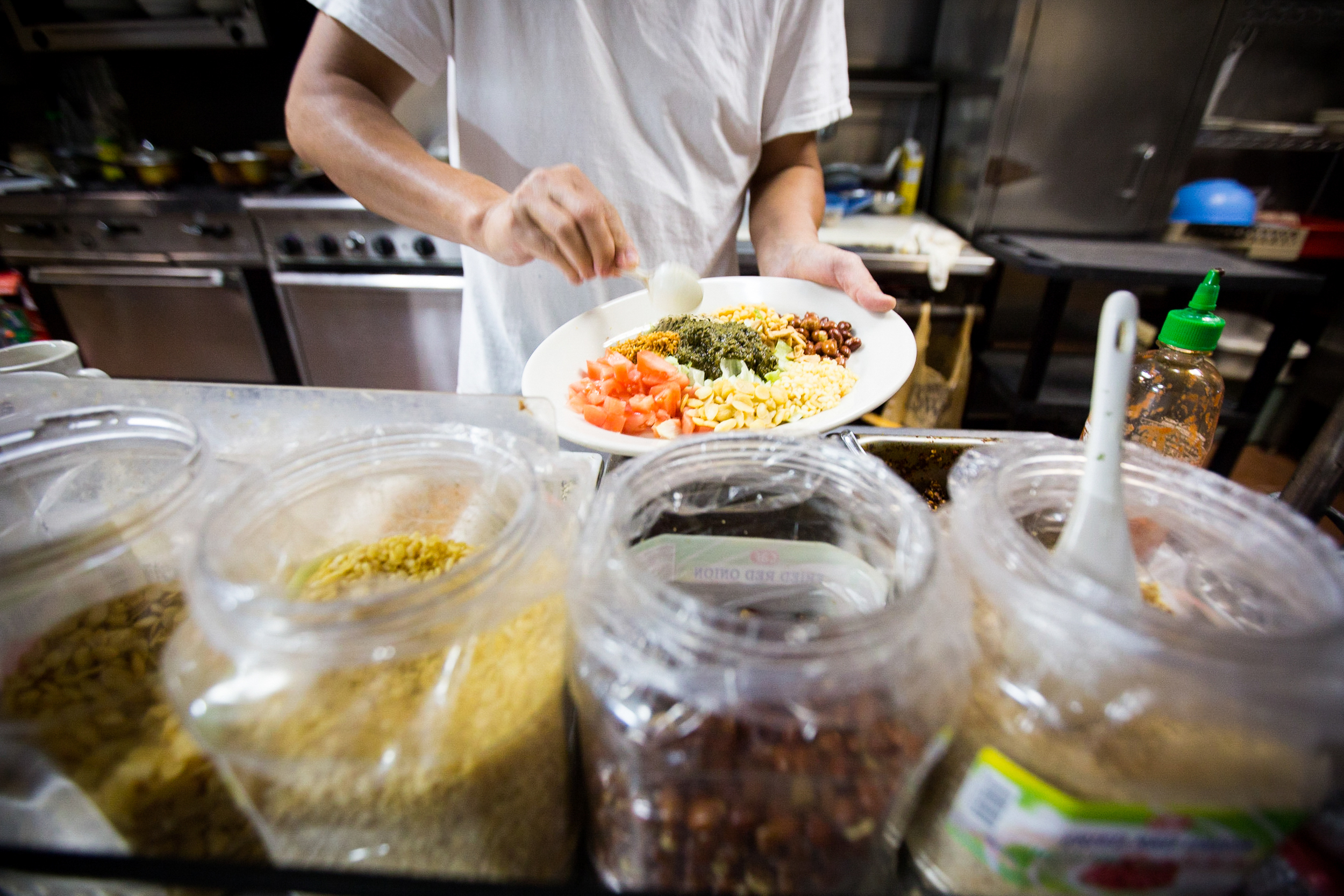 """Sai Kyaw, the owner and chef of Yoma restaurant, preparing signature dish the """"Tea Salad"""" in the kitchen of Yoma in Allston, Mass. Photo by Ann Wang"""