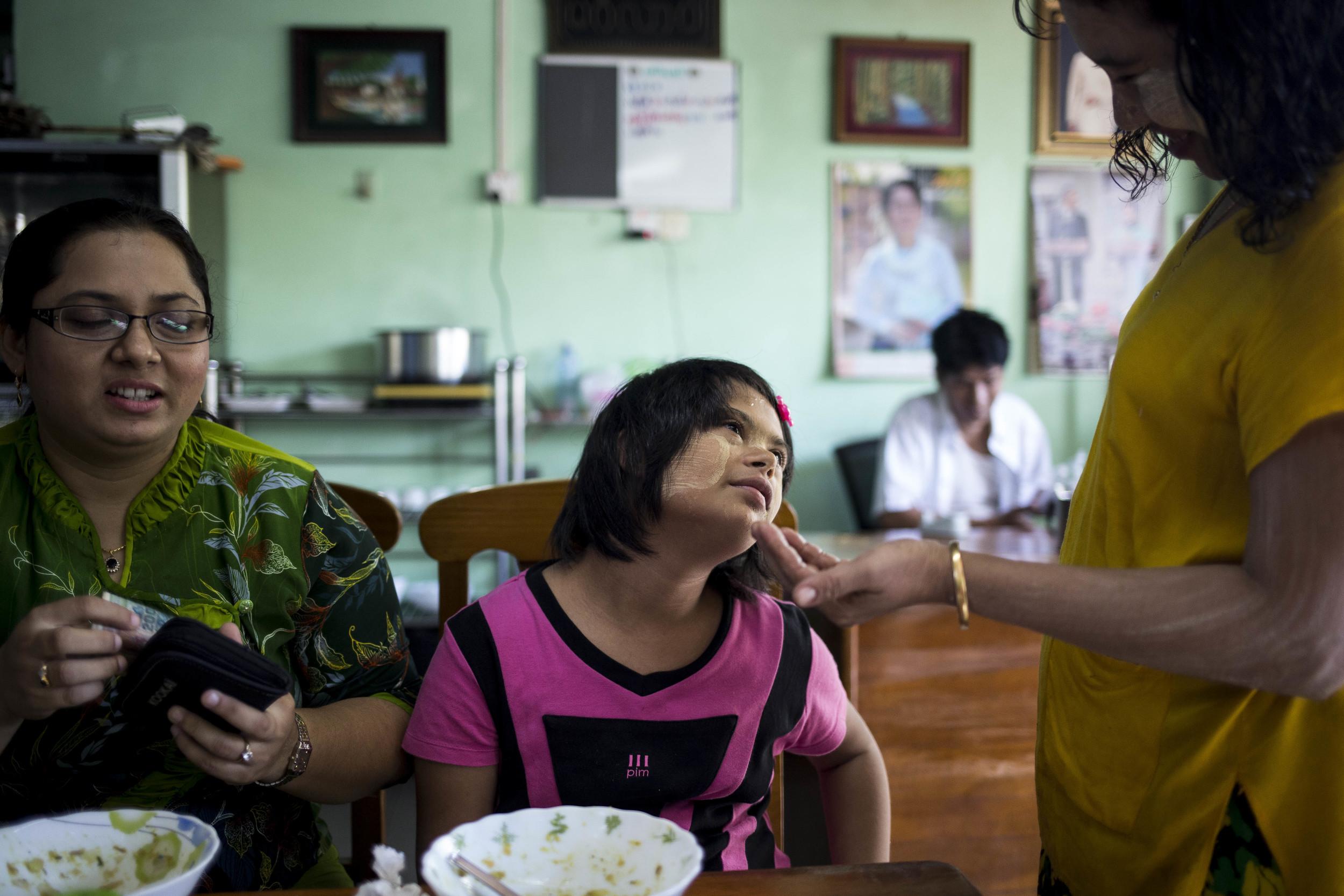 4.Kan Nay Chi Khin interacting with a stuff at a restaurant. People in Myanmar generally have no knowledge about Down syndrome, but because the family comes to this restaurant very often. The stuff is really familiar with Nay Chi. Photo by Ann WangBy following a couple of families with Down Syndrome children or adults, this project aim to show the limited resources these families have, which includes the county does not have facilities training special needs teacher,  and discrimination against disable people, causing people with Down Syndrome in Myanmar rarely receives education. Yet, the families of the Down Syndrome children determent to make a change, with or without the help from the government.