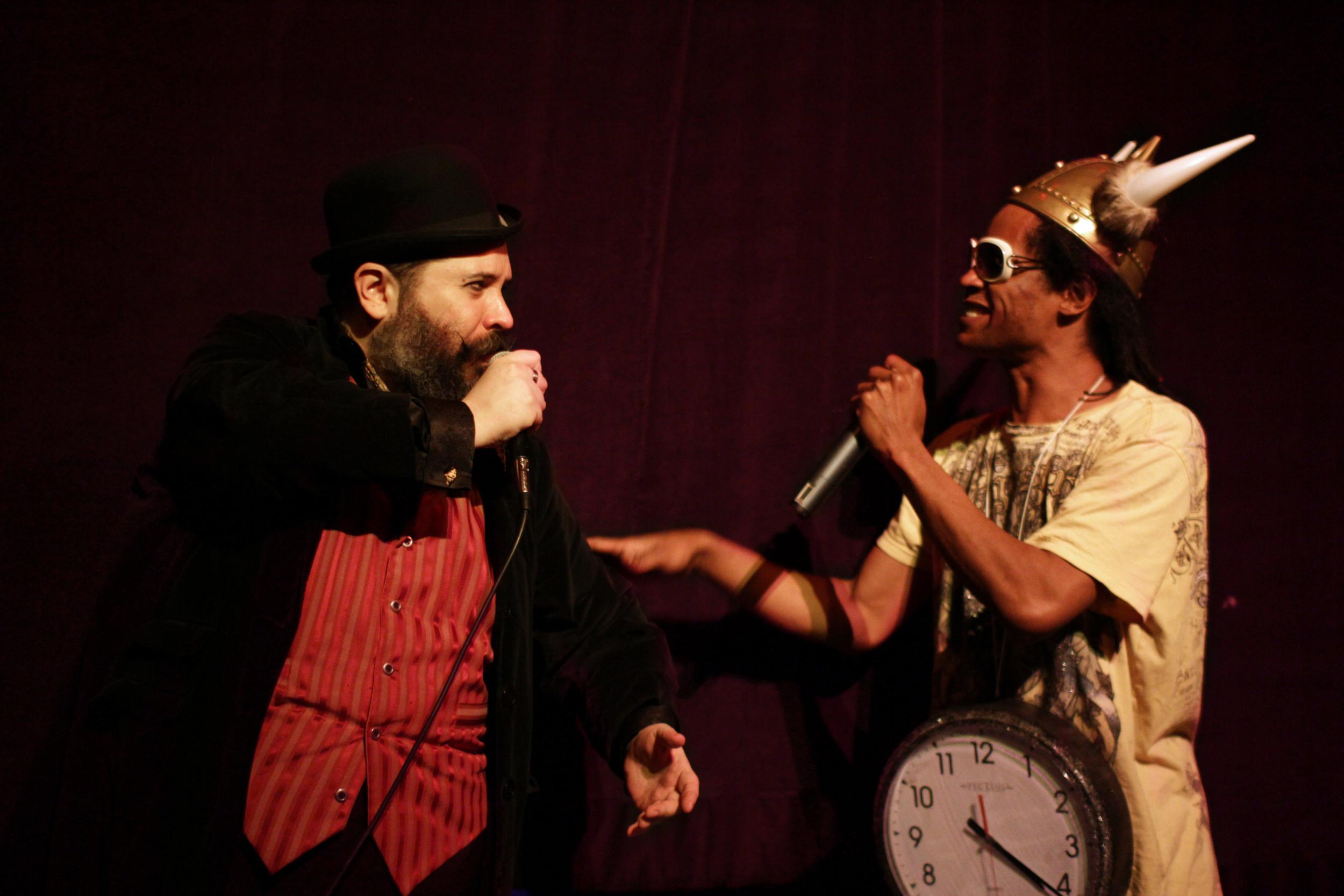 David Slone  as Charles Darwin, and  Kay Mazing  as Flava Flav.   ©CBMarney