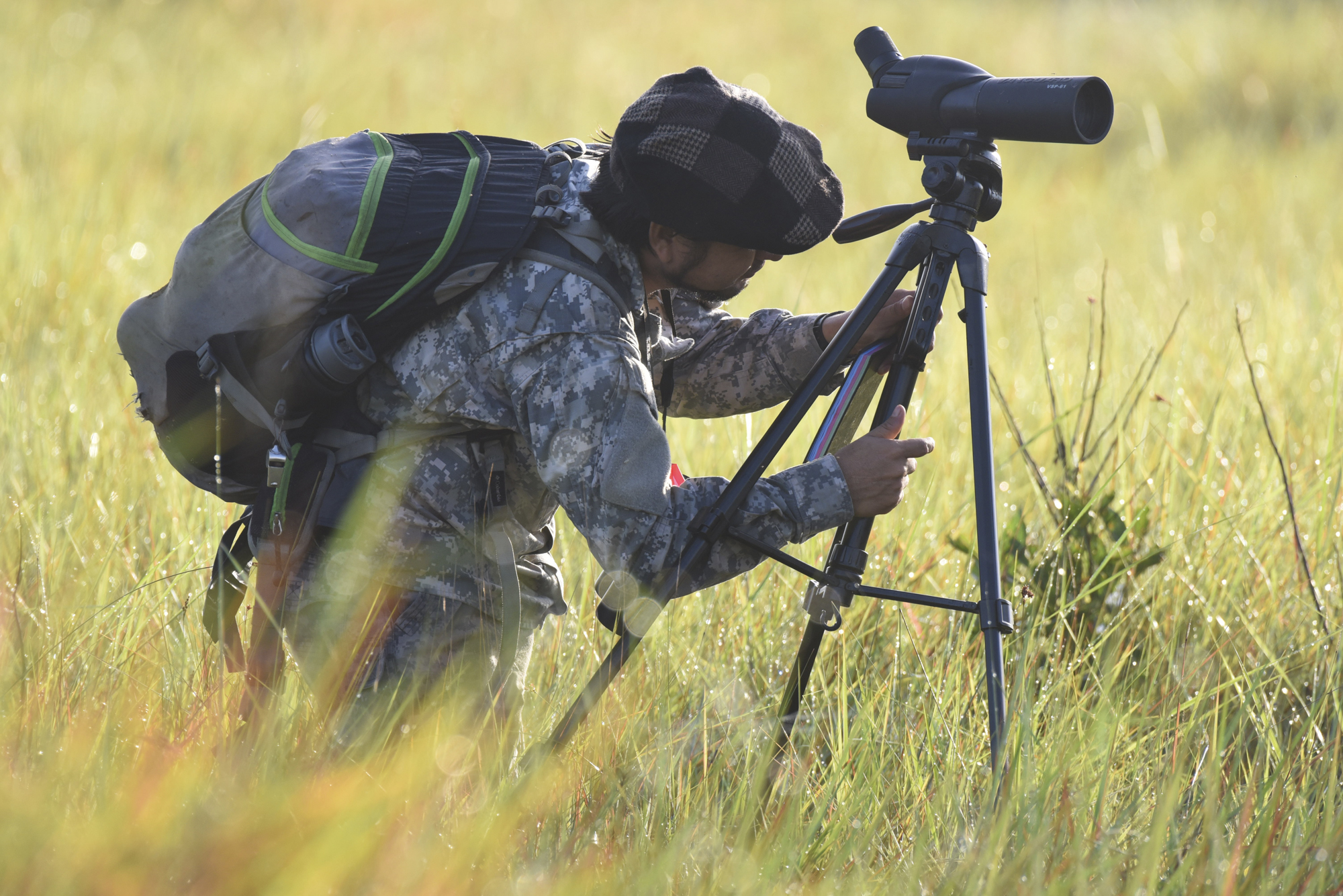 Yohamir adjusts his scope's tripod.