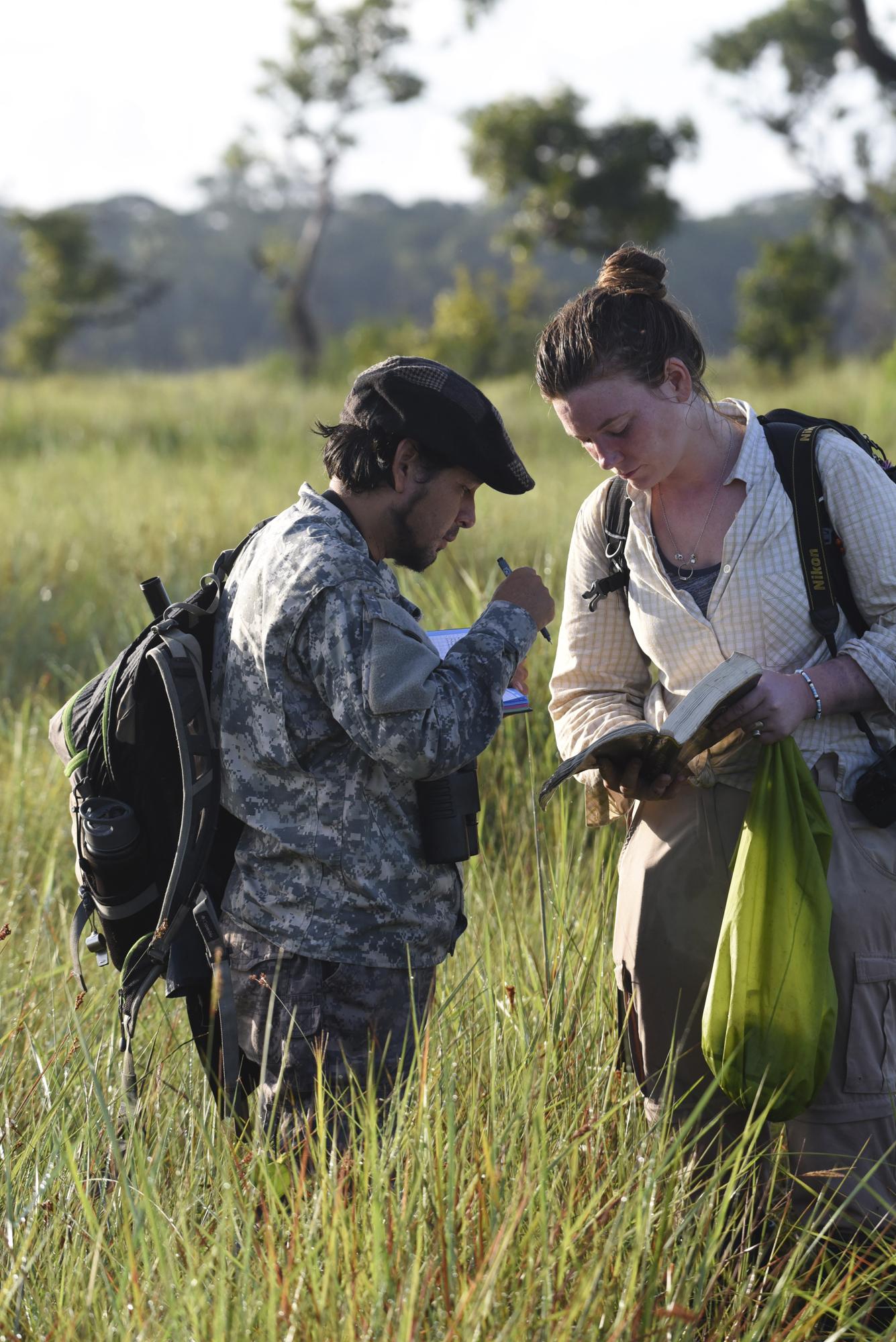 """Maisie helps Yohamir find a species in the """"Birds of Peru"""" guidebook."""