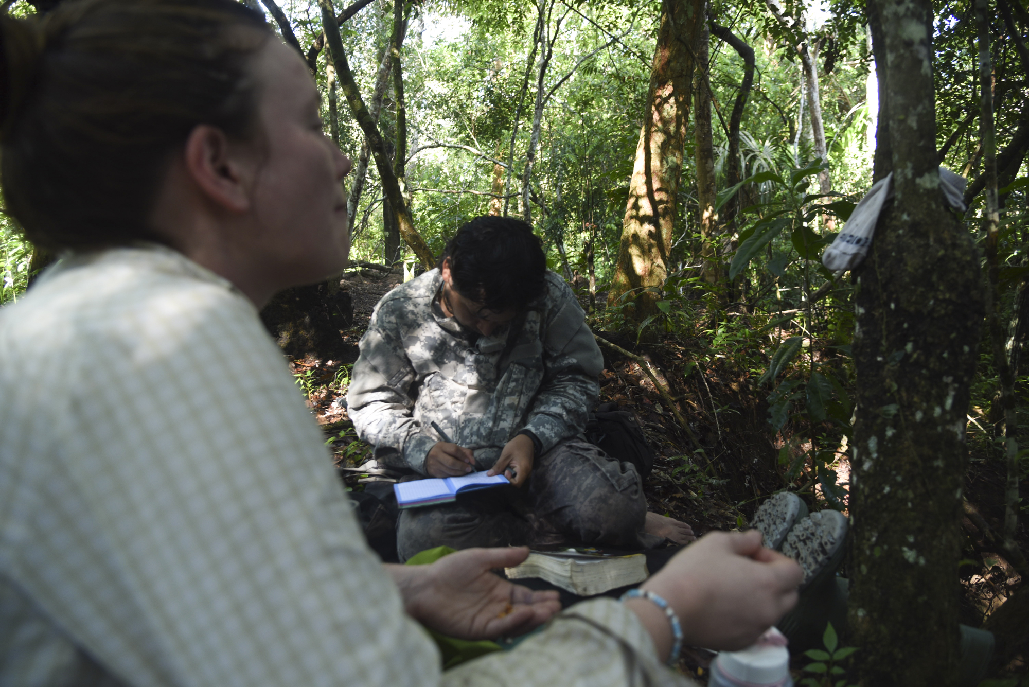 Maisie snacks while Yohamir takes notes about his day's sightings in a small gallery forest.
