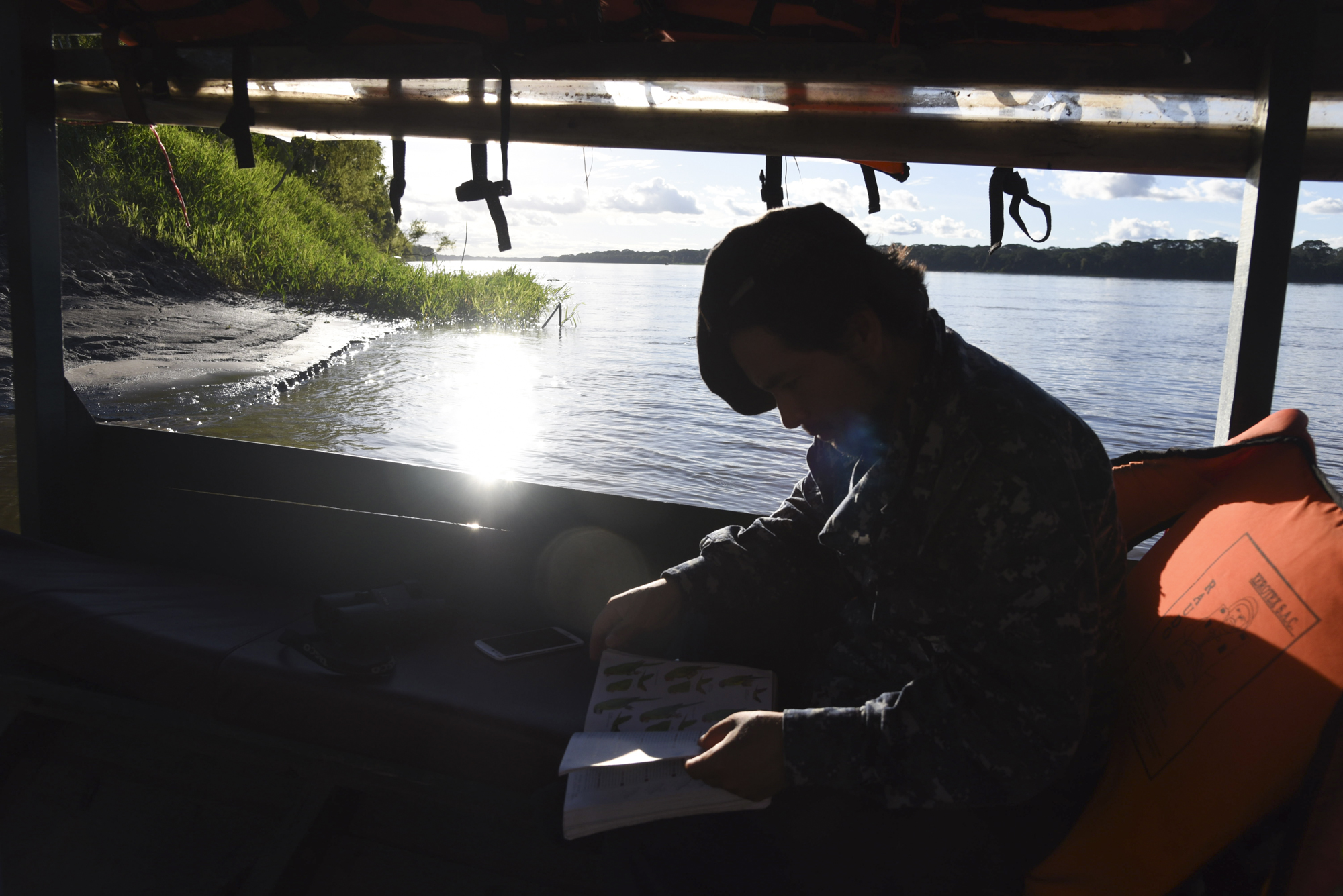 """After registering his Global Big Day results, Yohamir continues to study his """"Birds of Peru"""" book and search for more birds during the boat ride back to camp."""