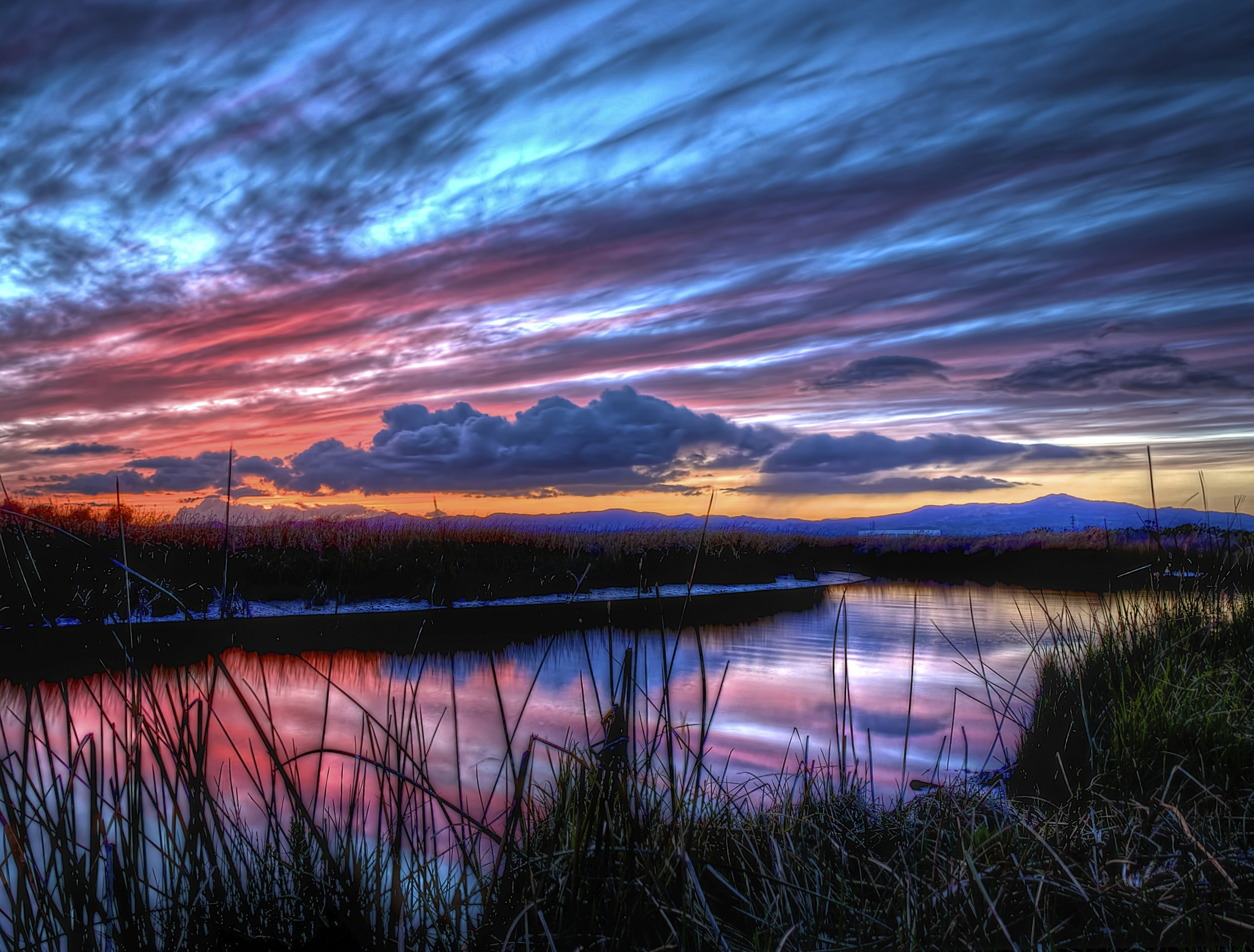 A cloudy sky yields a colorful sunset. Blue, pink and purple in the skies and reflected in the water.