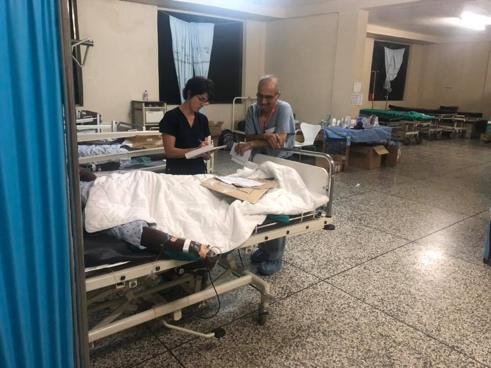 operation walk NY ghana joint surgery reviewing patient.jpg