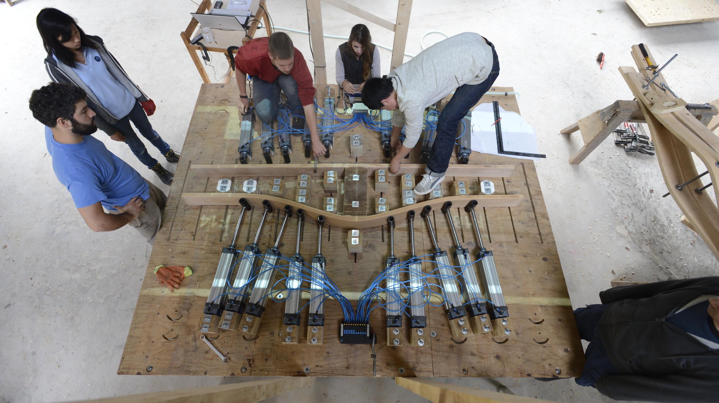 Hooke_Park_Design_&_Make_Timber_Seasoning_Shelter_bending_wood_on_the_jig_VB_2013_07_29_0040.JPG