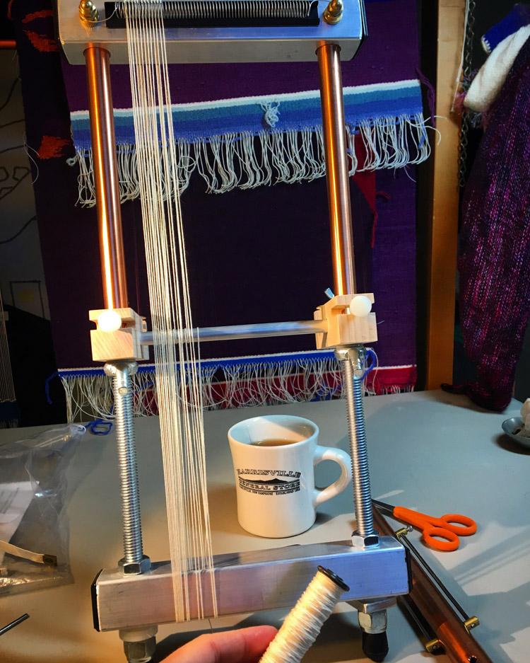 Lani Mirrix loom being warped. Tapestries waiting for finishing hanging behind...