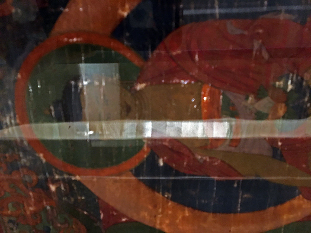 Painted side of Thangka through the table glass.