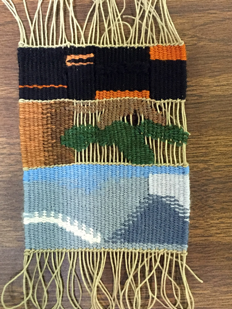 Liz wove a piece each day on the same loom. She wanted to respond to the environment and day one at the bottom was about clouds, the center one was woven after a long hike to Emmaline Lake when she was tired so she included the exposed warps in her interpretation of a tree to reflect that, and day 3 was about all the old burned trees around campus. She was thinking about the glossy black wood and reflecting that with a couple different fibers--both cotton and wool--which reflected the light differently (unfortunately difficult to see in this photo).