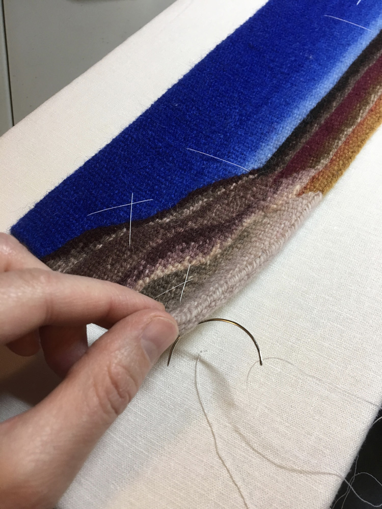 Using a curved needle to stitch the tapestry down