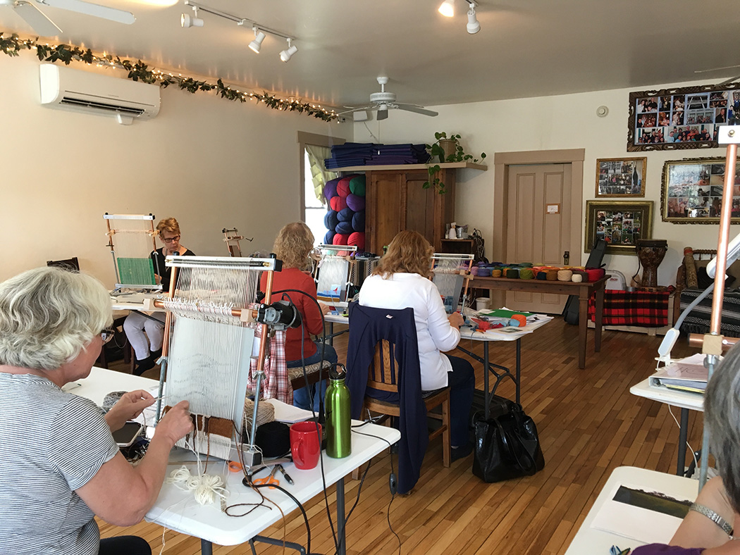 A group weaving in the Good Commons studio