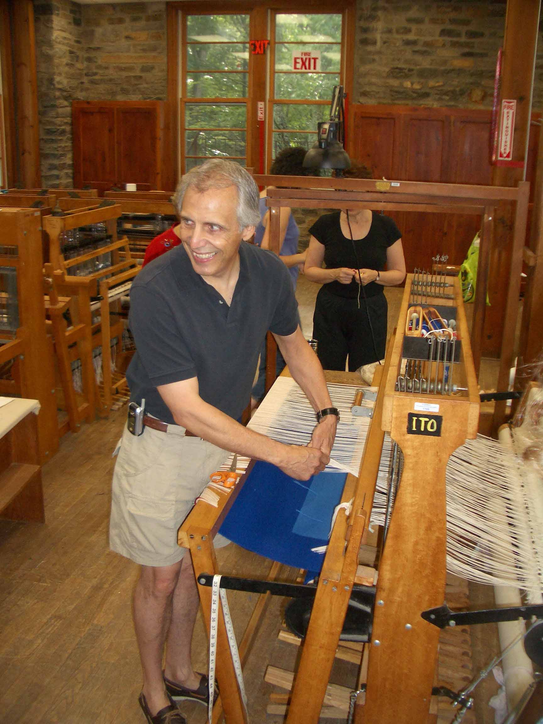 James Koehler, Penland School of Craft, 2005, cutting a Harmonic Oscillations tapestry off one of the school's Macomber looms