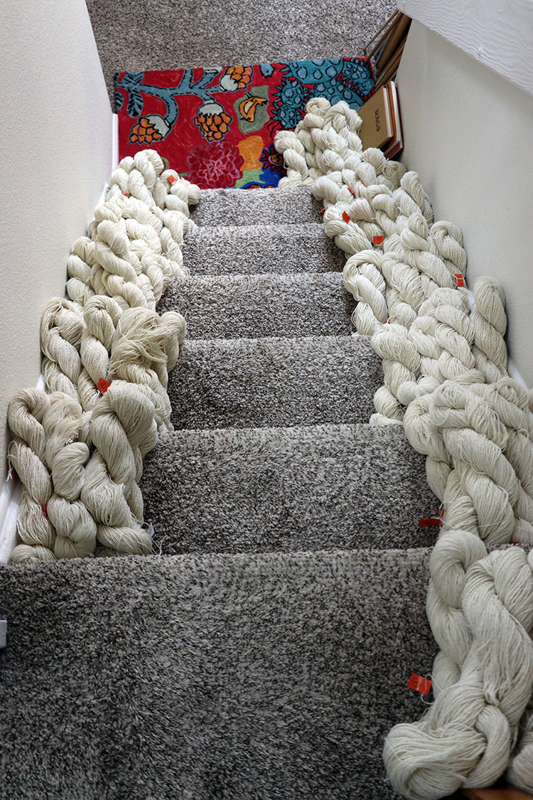Yarn waiting to be dyed sorted into colors. Stairs are useful this way.