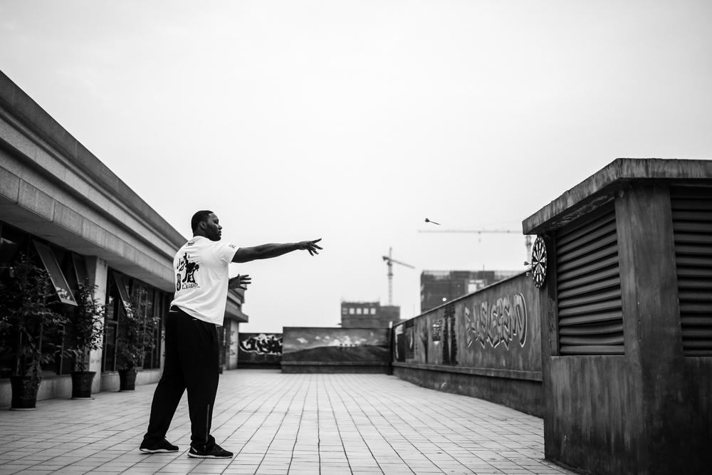Anthony Johnson plays darts on a rooftop in Chengdu, China.