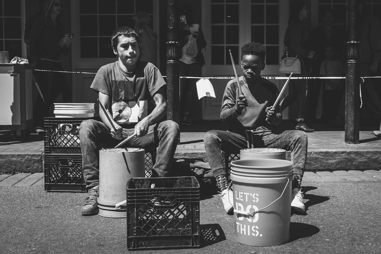 Two young boys play bucket drums on the streets of New Orleans, LA.