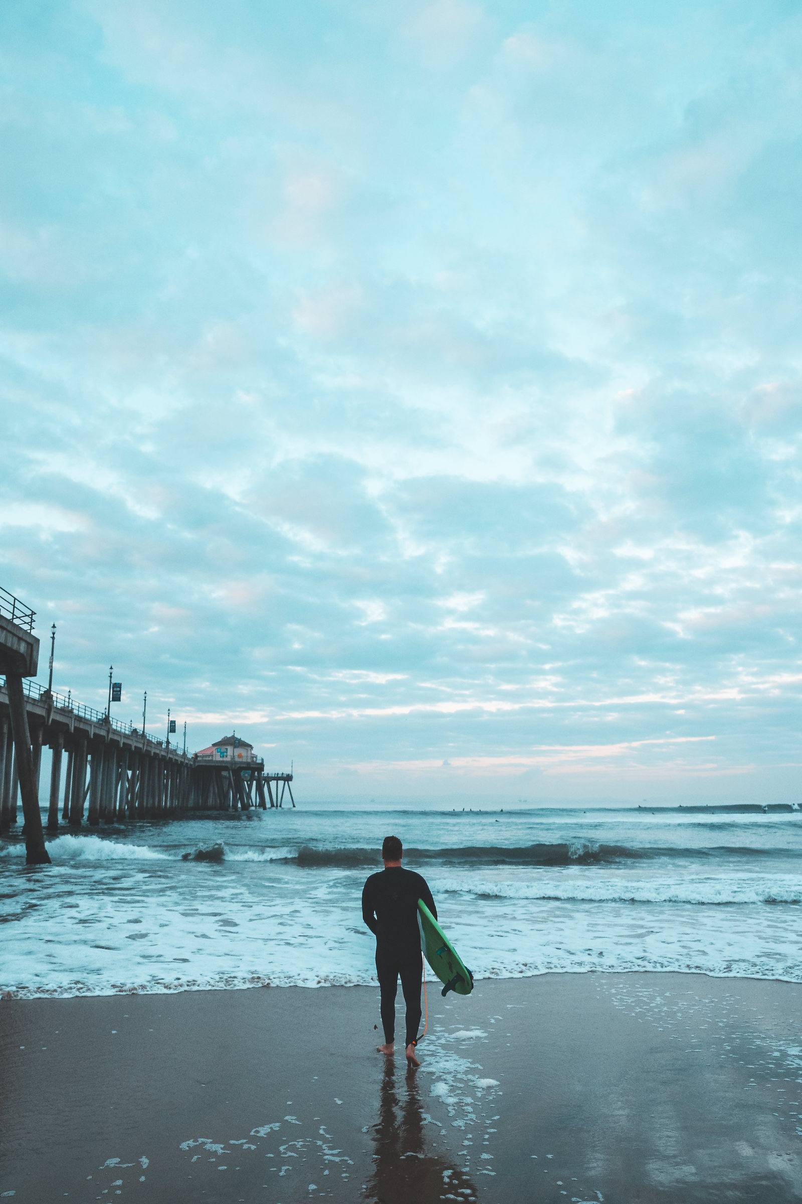 A surfer going out for a sunrise session in Huntington Beach, CA.