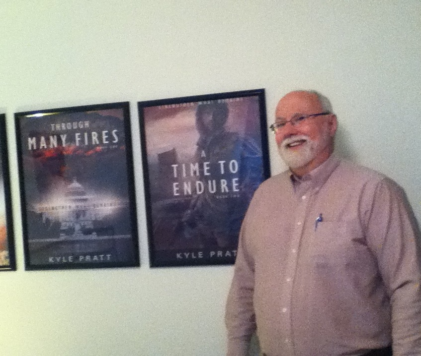 Kyle Pratt with posters of Through Many Fires and A Time to Endure.