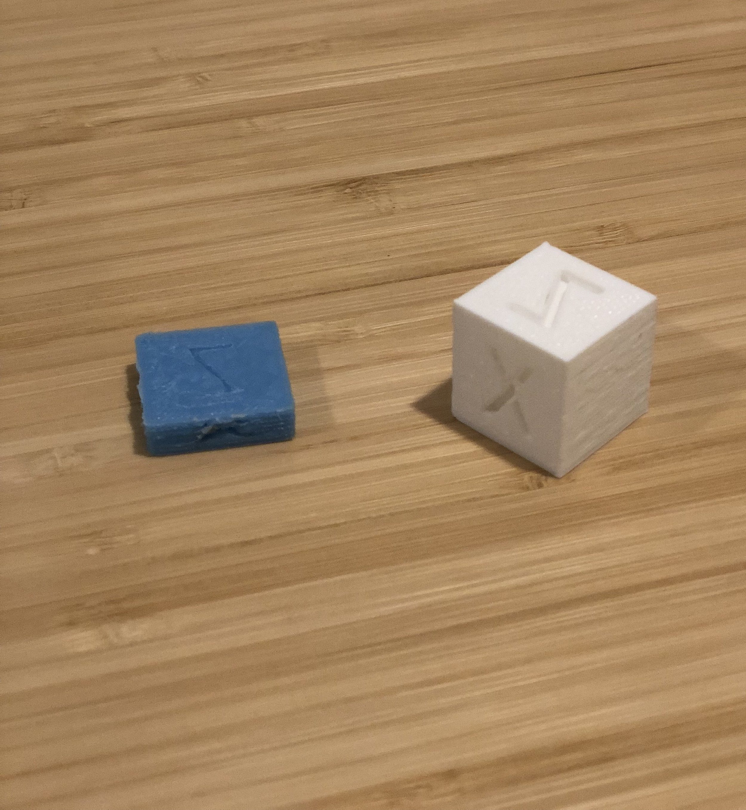 The white cube on the right is in the right range, dimensionally (20mm^3). The blue one on the left is 20mmx20mmx6mm.
