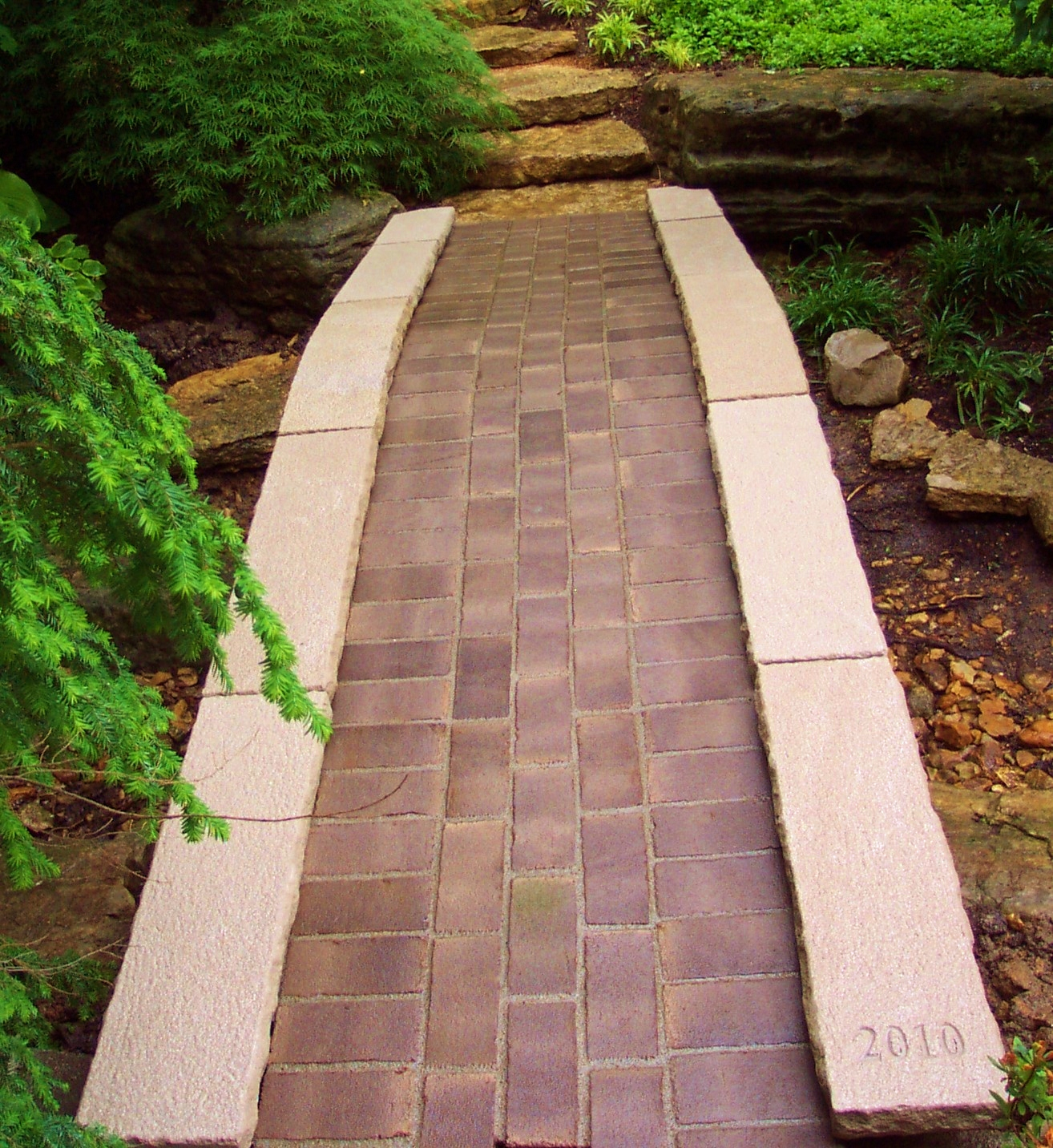 Stone arch bridge with a brick path inlay.  Stone Works  Lee Lindsey St. Louis, MO