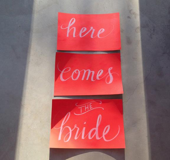 Robin + Johanna 's 11x17 hand-painted signs for kids to hold while marching down the aisle.