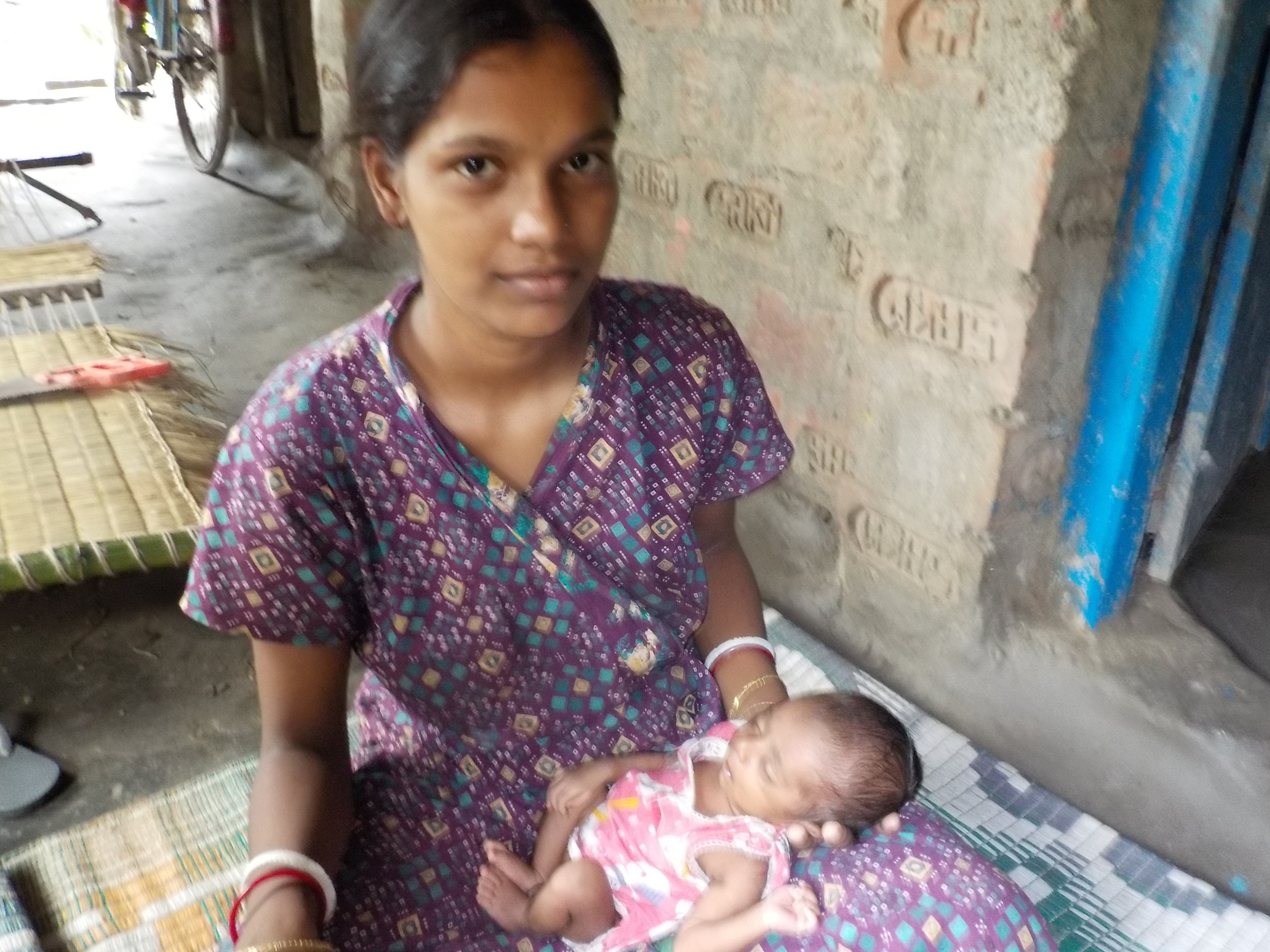 Teenage mother coddles a baby born at a low birth weight