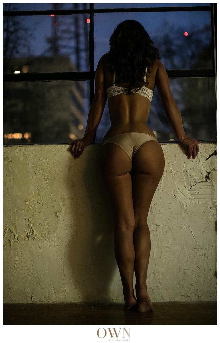 woman looking out a window boudoir session atlanta own boudoir
