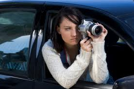 surveillance female hanging out of car with camera.jpg